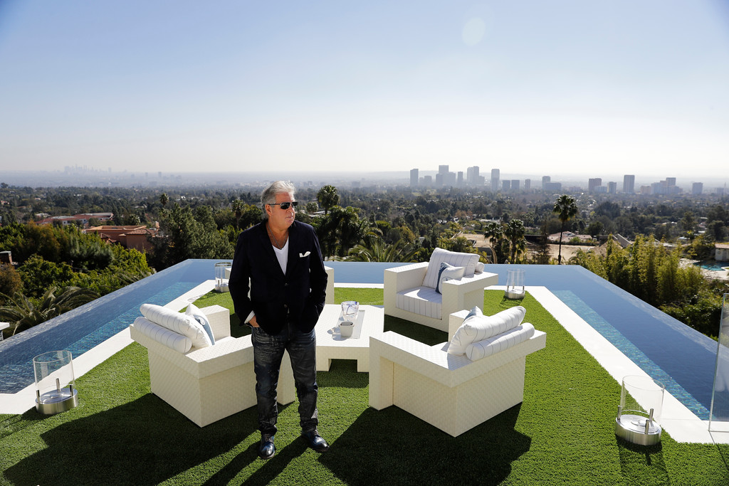 . In this Thursday, Jan. 26, 2017, photo, developer Bruce Makowsky poses for a photo on the balcony off the master bedroom of a $250 million mansion he built in the Bel-Air area of Los Angeles. The mansion, the most expensive home listed in the U.S., includes 12 bedroom suites, 21 bathrooms, five bars, three gourmet kitchens, a spa and an 85-foot infinity swimming pool with stunning views of Los Angeles. (AP Photo/Jae C. Hong)