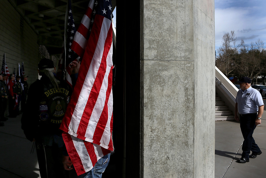 . A beam of light strikes the red and white stripes of the American Flag outside of the HP Pavilion in San Jose on Thursday where thousands of supporters met to pay their respects to SCPD detective Sgt. Loran \'Butch\' Baker and detective Elizabeth Butler. (Kevin Johnson/Sentinel)