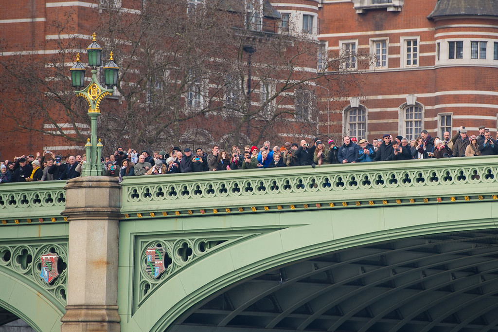. Crowds watch from Westminster Bridge as the Havengore makes its way along the River Thames during a recreation of the journey it made 50 years ago carrying the coffin of former prime minister Sir Winston Churchill during his state funeral in 1965, from the Tower of London to Westminster on January 30, 2015 in London, England. A series of events are to be held throughout the UK to mark the 50th anniversary of the death Britain\'s war time leader.  (Photo by Dominic Lipinski - WPA Pool/Getty Images)