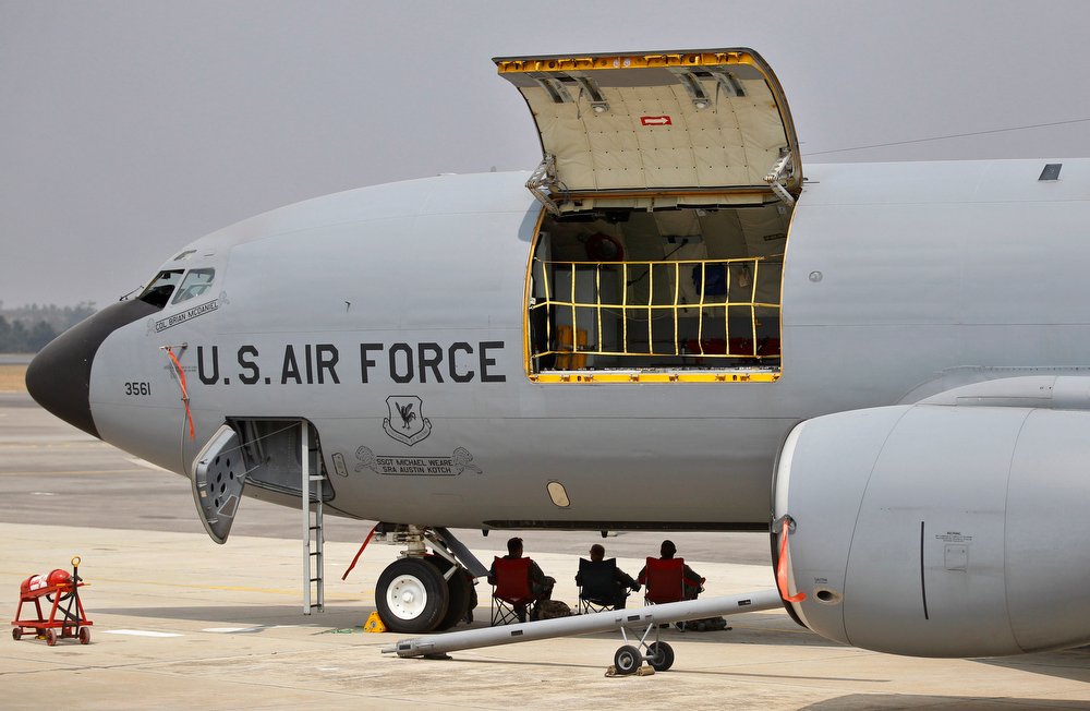 . U.S. Air Force personnel rest under the shade of a KC-135, an aerial refueling and transport aircraft, on the third day of the Aero India 2013 at Yelahanka air base in Bangalore, India, Friday, Feb. 8, 2013. More than 600 aviation companies along with delegations from 78 countries are participating in the five-day event that started Wednesday. (AP Photo/Aijaz Rahi)
