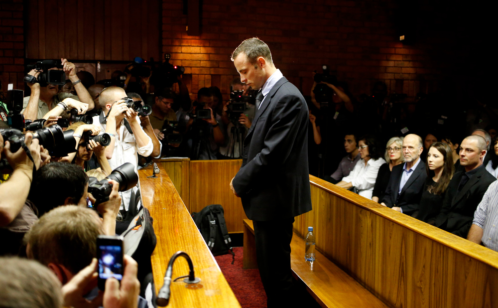 ". Oscar Pistorius stands at the dock before the start of proceedings at a Pretoria magistrates court February 22, 2013. ""Blade Runner\"" Pistorius, a double amputee who became one of the biggest names in world athletics, was applying for bail after being charged in court with shooting dead his girlfriend, 30-year-old model Reeva Steenkamp, in his Pretoria house.  REUTERS/Mike Hutchings"