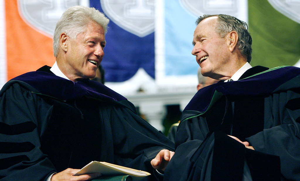 . Former Presidents Bill Clinton, left, and George H. W. Bush smile at each other on the podium at the Tulane University Commencement in New Orleans on Saturday May 13, 2006. (AP Photo/Alex Brandon, Pool)