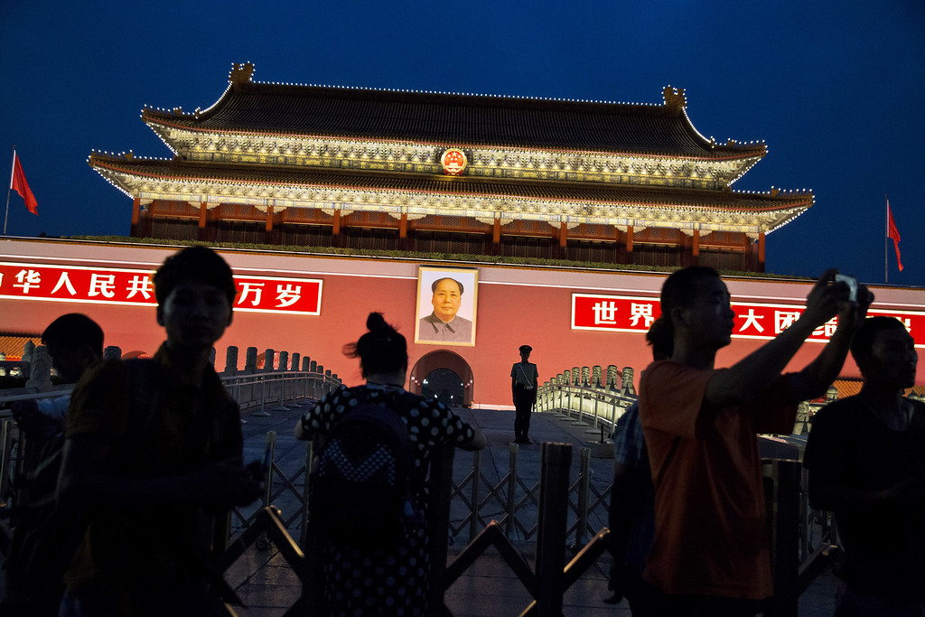 . A Chinese Paramilitary soldier stands guard under a portrait of the late leader Mao Zedong as tourists pass by in front of the Forbidden City at Tiananmen Square on June 4, 2014 in Beijing, China.  (Photo by Kevin Frayer/Getty Images)