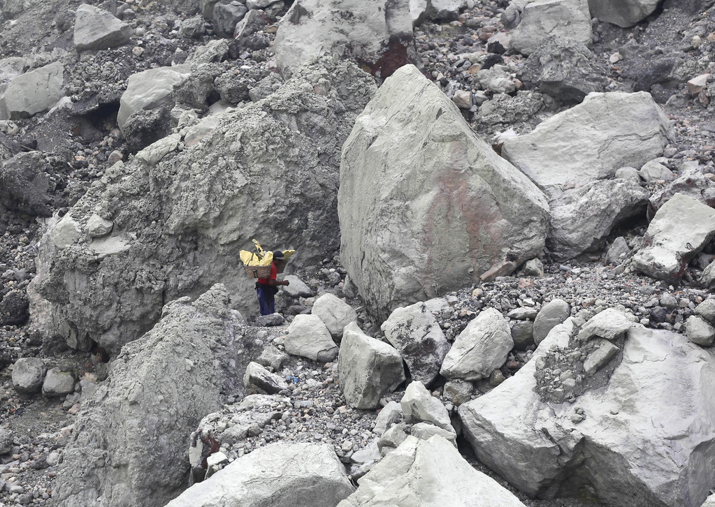 . In this April 16, 2016 photo, a sulfur miner is dwarfed by giant volcanic rocks as he carries baskets full of sulfur slabs on his shoulders up from the crater of Mount Ijen in Banyuwangi, East Java, Indonesia.  (AP Photo/Binsar Bakkara)