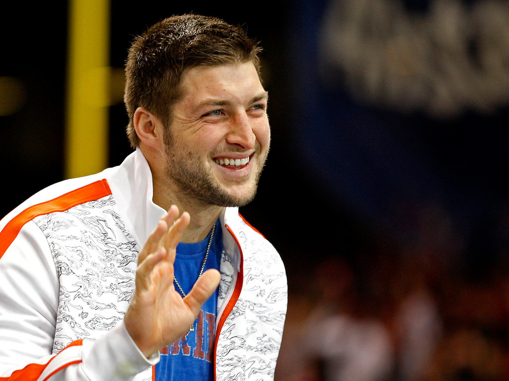 . Former Florida Gators quarterback Tim Tebow waves as he stands on the sidelines before the Gators play against the Louisville Cardinals in the 2013 Allstate Sugar Bowl NCAA football game in New Orleans, Louisiana January 2, 2013. Tebow now plays for the NFL\'s New York Jets.  REUTERS/Jonathan Bachman (UNITED STATES  - Tags: SPORT FOOTBALL)