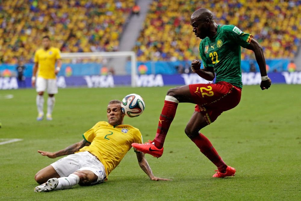 . Brazil\'s Dani Alves, left, blocks a shot by Cameroon\'s Allan Nyom during the group A World Cup soccer match between Cameroon and Brazil at the Estadio Nacional in Brasilia, Brazil, Monday, June 23, 2014. (AP Photo/Dolores Ochoa)