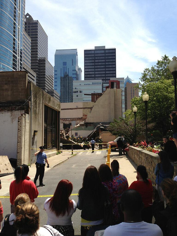 . In this photo provided by Jonathan Hudson, police keep onlookers behind yellow tape near a building collapse in downtown Philadelphia, Wednesday, June 5, 2013. The city fire commissioner says as many as eight to 10 people are believed trapped in the rubble. (AP Photo/Jonathan Hudson)