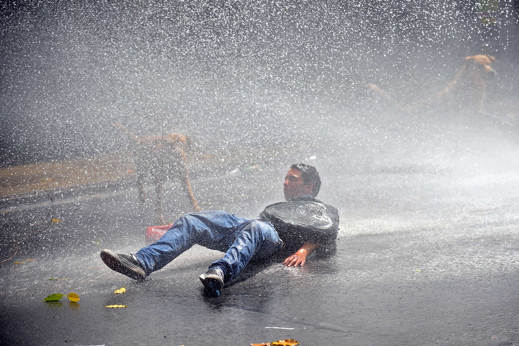 . A man falls on the ground after being hit by water during incidents after a march of Mapuche indigenous people in downtown Santiago, on October 12, 2013, during the commemoration of Columbus Day. HECTOR RETAMAL/AFP/Getty Images