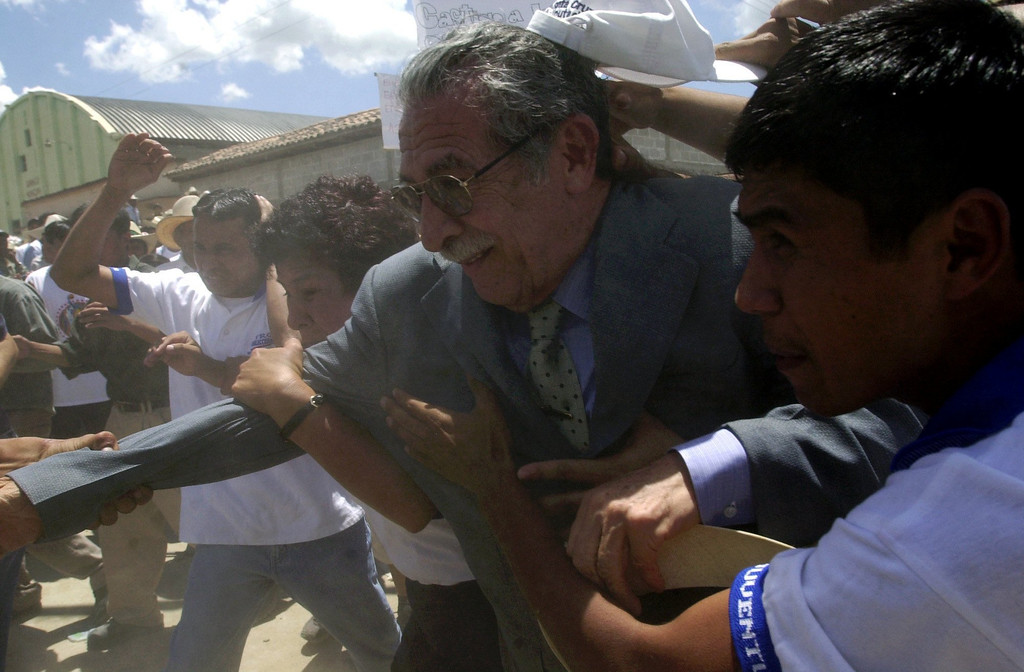 . Former dictator Efrain Rios Montt is protected by his bodyguards as he flees from the relatives of massacred villagers during a campaign rally in Rabinal, 180 km north from Guatemala City, June 14, 2003. (AP Photo/Rodrigo Abd)