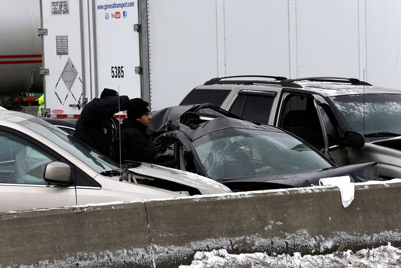 . Authorities search a section of multi-vehicle accident on Interstate 75 is shown in Detroit, Thursday, Jan. 31, 2013. Snow squalls and slippery roads led to a series of accidents that left at least three people dead and 20 injured on a mile-long stretch of southbound I-75. More than two dozen vehicles, including tractor-trailers, were involved in the pileups. (AP Photo/Paul Sancya)
