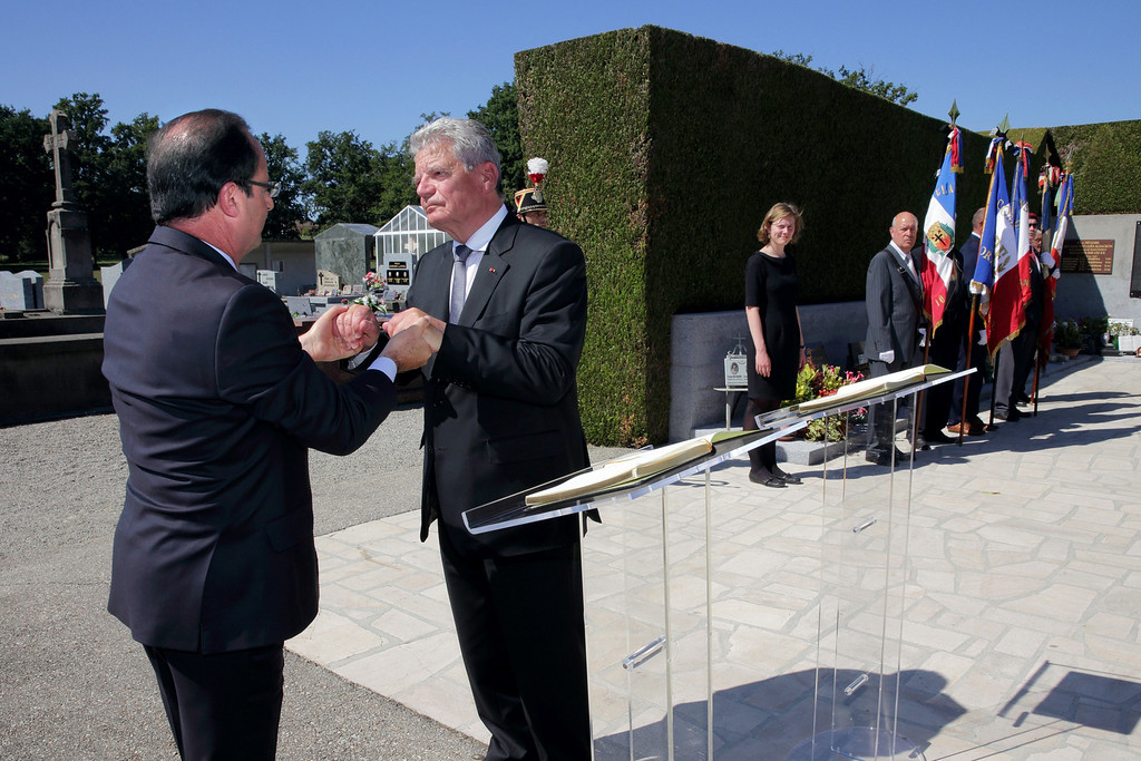 . French President Francois Hollande (L) and his German counterpart Joachim Gauck hold hands on September 4, 2013 after a ceremony at the cemetery of the central French village of Oradour-sur-Glane. The town has become a ghostly war crimes museum since Nazi troops burnt it to the ground on June 10, 1944. Six hundred and forty-two original inhabitants were massacred in Oradour and no one knows exacty why. Women and chldren were massacred in the church before their bodies were burnt by a German SS division. Hebras is one of three survivors still alive. PHILIPPE WOJAZER/AFP/Getty Images
