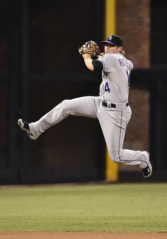 . SAN DIEGO, CA - SEPTEMBER 24:  Josh Rutledge #14 of the Colorado Rockies jumps but can\'t make the play on a single hit by Cameron Maybin #24 of the San Diego Padres during the fifth inning of a baseball game at Petco Park September, 24, 2014 in San Diego, California.  (Photo by Denis Poroy/Getty Images)