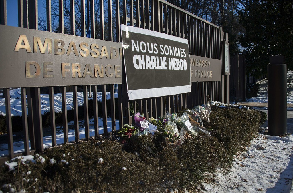 ". A banner written in French reads ""We Are Charlie Hebdo\"" hangs across the fence at the French Embassy over a flower memorial in Washington, DC, January 8, 2015, in response to the the satirical French magazine Charlie Hebdo\'s attack by three gunmen yesterday that took the lives of 12 people.    AFP PHOTO/JIM WATSON/AFP/Getty Images"