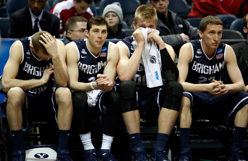 . BYU\'s Josh Sharp, left, Matt Carlino, Eric Mika, and Skyler Halford watch from the bench during the second half of a second-round game in the NCAA college basketball tournament Thursday, March 20, 2014, in Milwaukee. Oregon won 87-68. (AP Photo/Jeffrey Phelps)