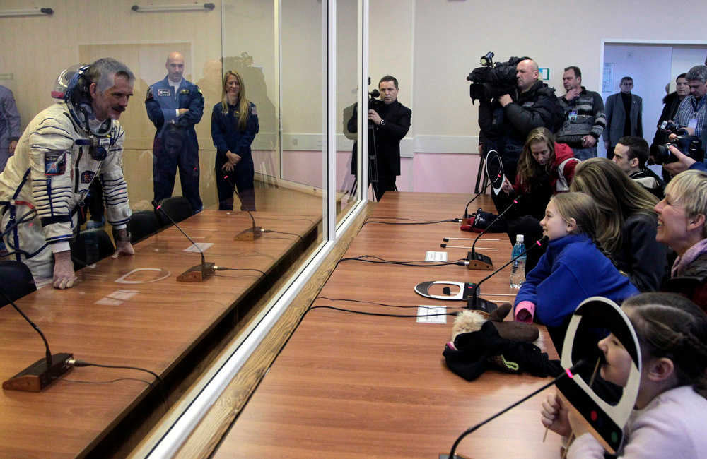 . Canadian astronaut Chris Hadfield, left, a member of the next expedition to the International Space Station, chats with friends and relatives during the pre-launch preparations at the Baikonur cosmodrome in Kazakhstan,Wednesday, Dec. 19, 2012. (AP Photo/ Maxim Shipenkov, Pool)