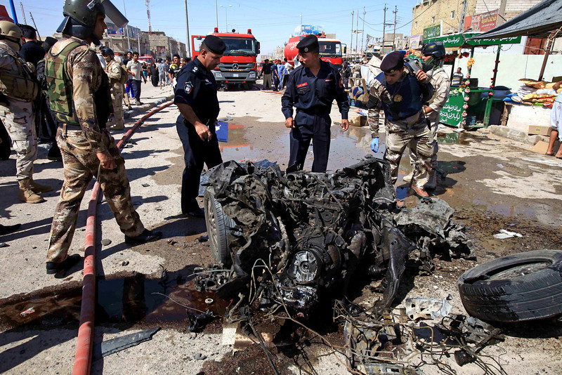 . Iraqi security forces inspects wreckage at the site of a car bomb explosion in Basra, 340 miles (550 kilometers) southeast of Baghdad, Iraq, Monday, July 29, 2013. A wave of over a dozen car bombings hit central and southern Iraq during morning rush hour on Monday, officials said, killing scores in the latest coordinated attack by insurgents determined to undermine the government. (AP Photo/Nabil al-Jurani)