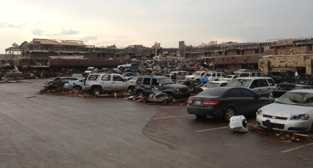 . A shopping center and parking lot are filled with debris after a huge tornado struck in Moore, Oklahoma near Oklahoma City, Oklahoma May 20, 2013. The huge tornado that struck the town of Moore, Oklahoma, on Monday was given a preliminary rating of at least EF4, or the second highest strength level, with winds of up to 200 miles per hour (321 kph), a U.S. government agency said.  REUTERS/Richard Rowe