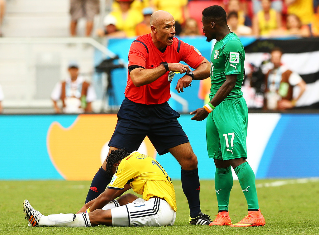 . Juan Guillermo Cuadrado of Colombia sits on the field as referee Howard Webb points to his watch and speaks to Serge Aurier of the Ivory Coast during the 2014 FIFA World Cup Brazil Group C match between Colombia and Cote D\'Ivoire at Estadio Nacional on June 19, 2014 in Brasilia, Brazil.  (Photo by Elsa/Getty Images)