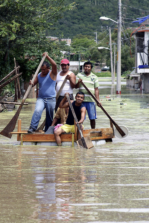 . Residents attemp to cross a flooded street using a makeshift raft in Chilpancingo, state of Guerrero, Mexico, on September 17, 2013. Mexican authorities scrambled Tuesday to launch an air lift to evacuate tens of thousands of tourists stranded amid floods in the resort of Acapulco following a pair of deadly storms. The official death toll rose to 47 after the tropical storms, Ingrid and Manuel, swarmed large swaths of the country during a three-day holiday weekend, sparking landslides and causing rivers to overflow in several states. EDUARDO GUERRERO/AFP/Getty Images