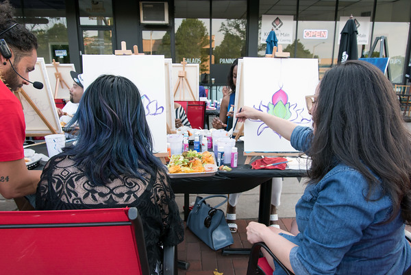 05/25/18 Wesley Bunnell   Staff Maria Morales, R, cleans her brush during an outdoor art class taught by artist Christian Yong on Friday night outside of KC's on Main. The program also featured waiter service and food from KC's and is called Patio Paint & Sit.
