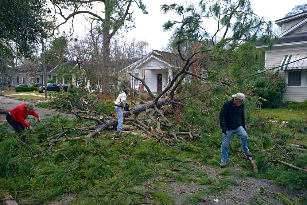 . Residents clean up downed trees and limbs and assess the damage from a Christmas Day tornado Wednesday, Dec. 26, 2012  in Mobile, Ala. With only a handful of injuries and no deaths reported statewide from the storms, the head of the state\'s emergency response said it was difficult to fathom how the toll wasn\'t worse. (AP Photo/G.M. Andrews)