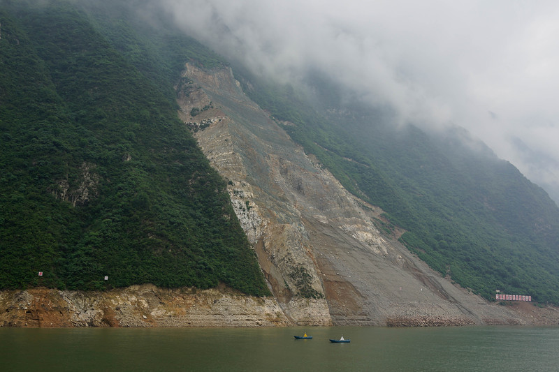 "Yangtze River - huge landslide caused by the washing away of subjacent trees and foliage.  Landslide halts Yangtze River cruise (Xinhua) 23:51, October 23, 2011     CHONGQING - A landslide in southwest China's Chongqing municipality blocked part of the Yangtze River's navigation route Friday, forcing the cancellation of a river cruise for multitudes of tourists, local authorities said Saturday.  The landslide happened at around 7 am Friday in Liangping township of Wushan county, said an officer with Chongqing's armed police headquarters who joined the river cleanup and helped evacuate tourists.  Although there were no casualties, the officer said cruise and ferry services from Wushan to Yichang, where the landmark Three Gorges Dam is located in the central Hubei province, were canceled, and there is no timetable as to when the route would reopen.  The county government sent a fleet of buses to transport tourists, all of whom were evacuated as of Saturday afternoon, he said.  ""We were woken up and ushered off the ship at 4 am Friday,"" said an Internet user surnamed ""beijingshaniuer"" on Sina Weibo, a popular Twitter-like microblogging service. ""We then spent nine hours on a bus to Yichang. It was drizzling the entire time.""  A cruise along the Yangtze River remains trendy in China, particularly in spring and fall. A downstream cruise from Chongqing to Yichang takes four days, whereas the upstream cruise normally takes five days.  Source: http://english.peopledaily.com.cn/90882/7624112.html  Yangtze landslide near Three Gorges Dam 'won't block river': experts www.chinaview.cn  2009-04-07 23:36:38	 	  Print     CHONGQING, April 7 (Xinhua) -- A landslide on a section of the bank of China's Yangtze River near the Three Gorges Dam may fall into the river but will not block it, experts said Tuesday.      Cracks had been seen in the landslide and its shape had continued to change, said Yin Yueping, deputy chief of the investigation team, deputy general engineer of China Geological Survey.      Traffic on the river will not be stopped although the landslide may fall into the river, Yin said.      The landslide will be monitored round the clock, said Zhou Shihong, deputy director of the municipal Bureau of Land and Resources.      A portion of the river's southern bank in Guling township, Yunyang County of southwest China's Chongqing Municipality broke loose from the rest of the bank since November last year, when the cofferdams of the Three Gorges Dam tried to hold water at a depth of 175 meters, Zhou said.      The dislocation had worsened since March and quickened pace in recent days, Zhou said.      The 55 people living on the sliding portion, called the Liangshuijing landslide, have been evacuated.      According to the observation center, the soil in the landslide is estimated to be 3.6 million cubic meters, covering 100,000 square meters.      Nearly 10,000 vessels pass through this section of river each year, about 300 vessels per day with 23,000 passengers per day.      Eight coastguard vessels had been working on the river and no casualties or accidents had been reported, Zhou said.  Source: http://news.xinhuanet.com/english/2009-04/07/content_11145630.htm"
