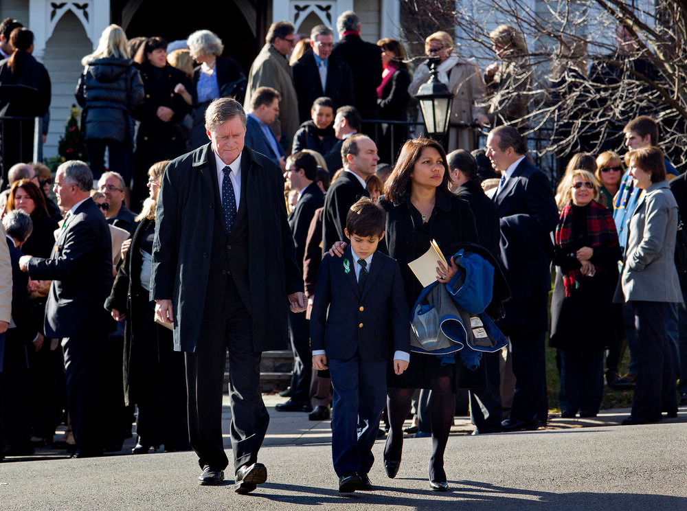 Description of . A young mourner is escorted from the funeral of teacher Anne Marie Murphy at the St. Mary Of The Assumption Church in Katonah, N.Y. Thursday, Dec. 20, 2012. Murphy was killed when Adam Lanza, walked into Sandy Hook Elementary School in Newtown, Conn., Dec. 14, and opened fire, killing 26, including 20 children, before killing himself. (AP Photo/Craig Ruttle)