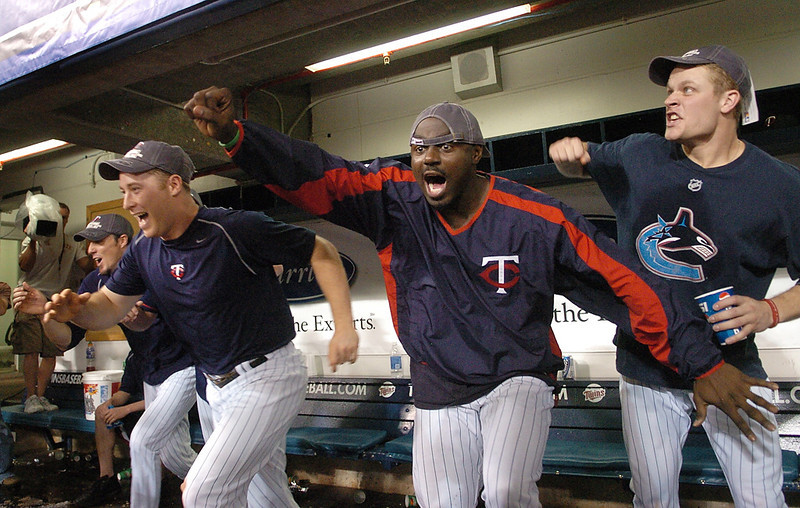 . Twins players, left to right, Joe Nathan, Lew Ford, Rondell White and Justin Morneau rush the Metrodome field after the final out of the Tigers-Royals game Sunday, October 1, 2006. The Royals\' victory gave the Twins the American League Central Division title. (File photo)