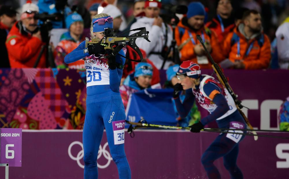 . Finland\'s Kaisa Makarainen, left, shoots as Norway\'s Tora Berger, background, leaves the shooting range during the women\'s biathlon 10k pursuit, at the 2014 Winter Olympics, Tuesday, Feb. 11, 2014, in Krasnaya Polyana, Russia. (AP Photo/Gero Breloer)