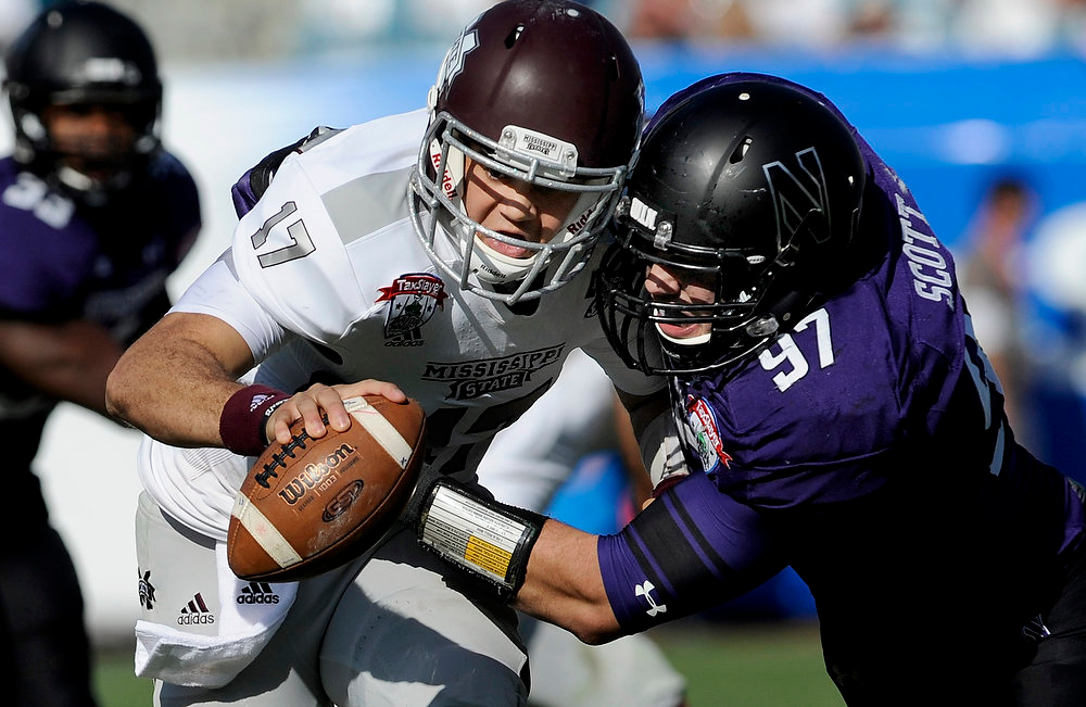 . Mississippi State quarterback Tyler Russell (17) is sacked by Northwestern defensive lineman Tyler Scott (97) during the second half of the Gator Bowl NCAA college football game, Tuesday, Jan. 1, 2013 in Jacksonville, Fla. Northwestern won 34-20. (AP Photo/Stephen Morton)