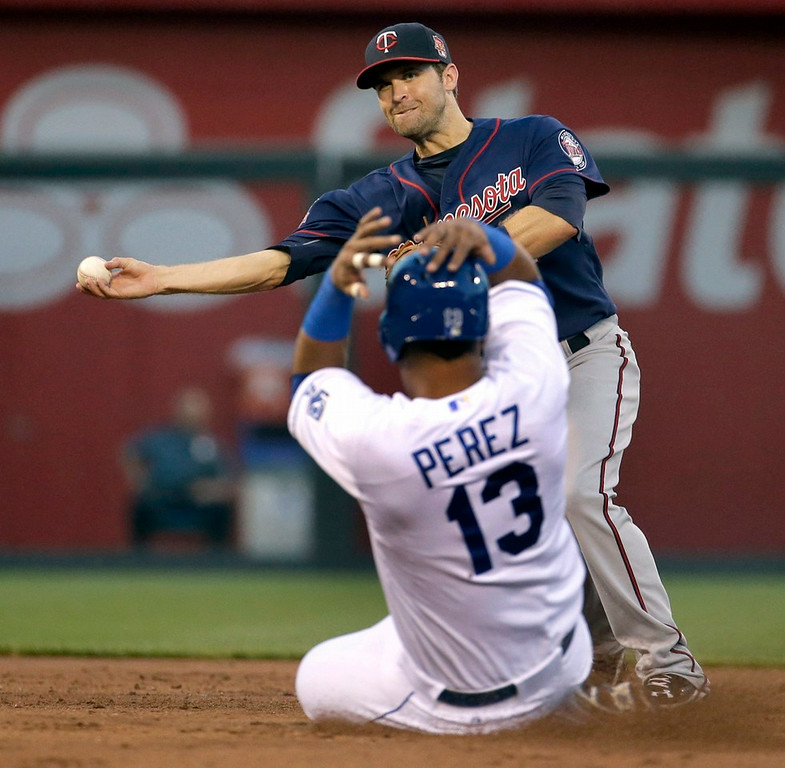 . Twins second baseman Brian Dozier throws to first to complete a double play hit into by Kansas City\'s Josh Willingham, after forcing Salvador Perez out at second, during the first inning. (AP Photo/Charlie Riedel)