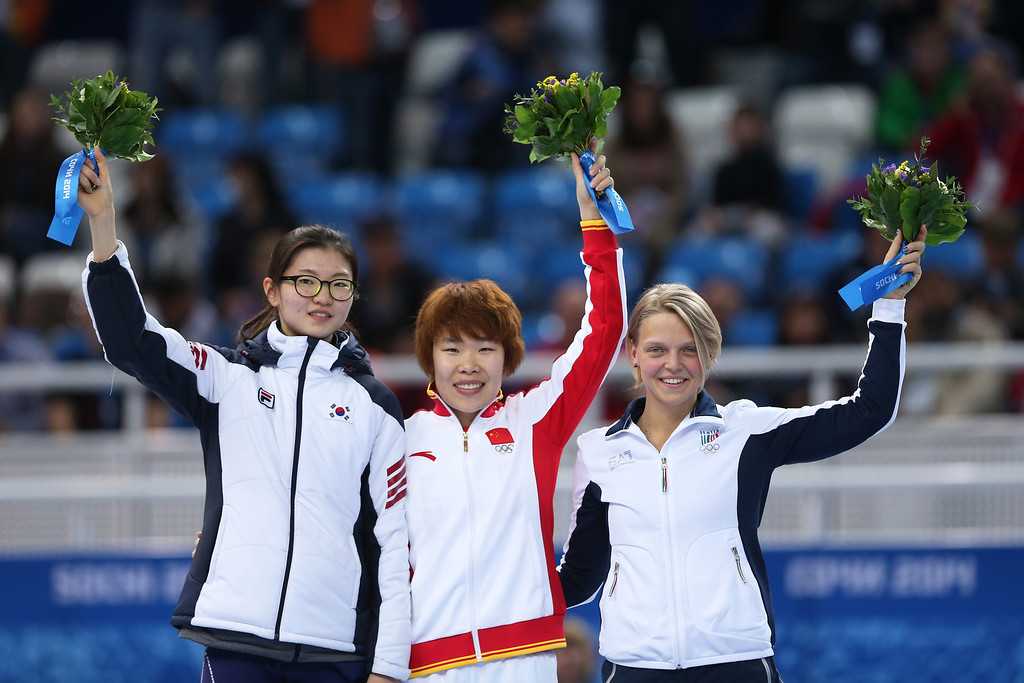 . SOCHI, RUSSIA - FEBRUARY 15:  Gold medallist Yang Zhou (C) of China stands on the podium during the flower ceremony with silver medallist Suk Hee Shim (L) of South Korea and bronze medallist Arianna Fontana of Italy after the Ladies\' 1500 m Final Short Track Speed Skating on day 8 of the Sochi 2014 Winter Olympics at the Iceberg Skating Palace on February 15, 2014 in Sochi, Russia.  (Photo by Matthew Stockman/Getty Images)