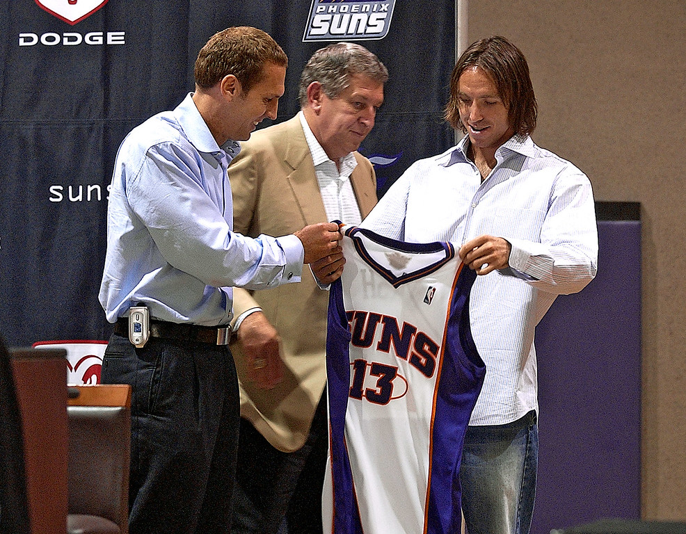 . Newly aquired Phoenix Suns guard Steve Nash, right, holds up his new jersey as Suns\' President Bryan Colangelo, left, and CEO Jerry Colangelo watch Wednesday, July 14, 2004 at America West Arena in Phoenix.  (AP Photo/Matt York)