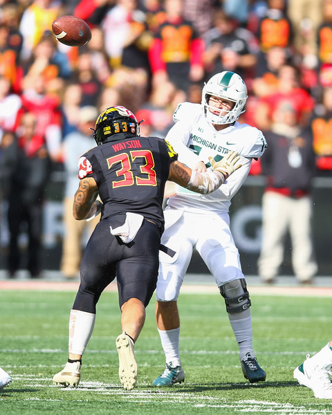 Michigan State quarterback #14 Brian Lewerke throws a pass under pressure from Maryland DB #33 Tre Watson