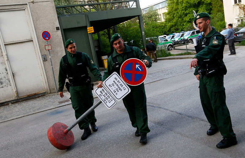 . German riot police install a traffic sign in front of a courthouse, where the trial against Beate Zschaepe, a member of the neo-Nazi group National Socialist Underground (NSU), began in Munich on May 6, 2013. The surviving member of NSU blamed for a series of racist murders that scandalized Germany and shamed its authorities goes on trial on Monday in one of the most anticipated court cases in recent German history. The trial in Munich will focus on 38-year-old Zschaepe, who is charged with complicity in the murder of eight Turks, a Greek and a policewoman between 2000-2007, as well as two bombings in immigrant areas of Cologne, and 15 bank robberies. Four others charged with assisting the NSU will sit with Zschaepe on the bench. REUTERS/Kai Pfaffenbach