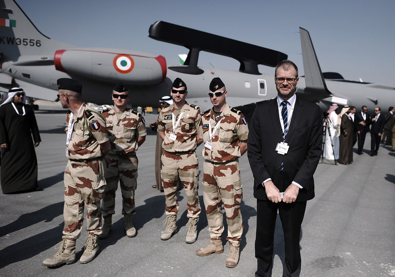 . French Ambassador to Bahrain Christian Testot (R) stands near  the French air show team (MIRAG 2000) during the opening of the Bahrain International Airshow 2014, in Sakhir, south of the capital Manama, on January 16, 2014. (MOHAMMED AL-SHAIKH/AFP/Getty Images)