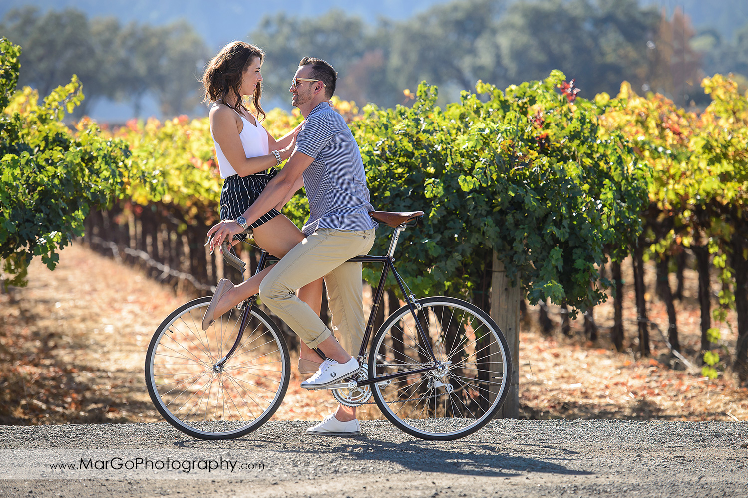 full body portrait of man in blue shirt and woman in white top and navy blue shorts sitting on the bicke in front of vineyard during Napa Valley engagement session at Grgich Hills Estate in Rutherford
