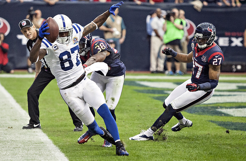 . Reggie Wayne #87 of the Indianapolis Colts completes a pass in the endzone as he beats Danieal Manning #38 and Quintin Demps #27 of the Houston Texans on the play in the first half at Reliant Stadium on December 16, 2012 in Houston, Texas. The play was negated by a penalty.  (Photo by Bob Levey/Getty Images)