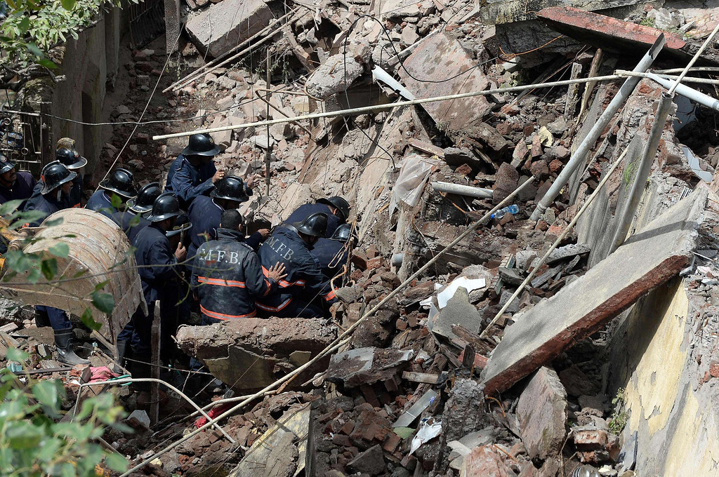 . Firefighters look for survivors through a clearing amidst the rubble of the building collapse in Mumbai on September 27, 2013. AFP PHOTO/Indranil  MUKHERJEE/AFP/Getty Images