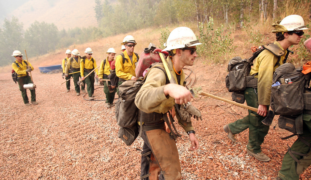. Members of the Ironwood Hot Shots from Tuscon, Ariz. move out after cutting a fire line behind homes as the Elk Complex fire burns in Pine, Idaho, Monday, Aug. 12, 2013. Red fire retardant is shown on the ground from an air drop. (AP Photo/The Idaho Statesman, Joe Jaszewski)