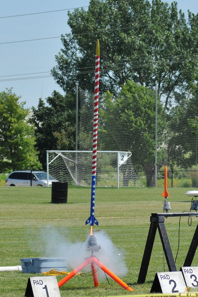 Matt Joseph's Estes Mean Machine, with an Independence Day paint scheme, lifts off with a D12-5 motor.  Photo by Alan M. Carroll