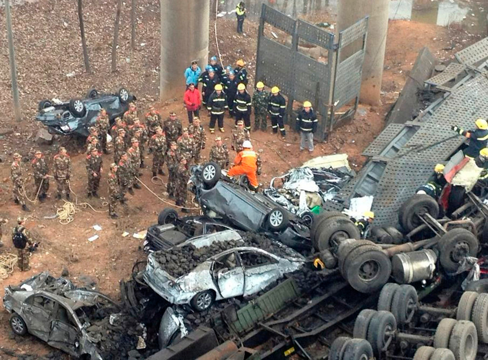 . Rescuers look for survivors near the wreckage of vehicles after a expressway bridge partially collapsed on the Lianhuo highway in Mianchi county, Henan province February 1, 2013. According to Xinhua News Agency, five people have died and eight others were injured after an expressway bridge partially collapsed due to a truck explosion Friday morning in central China\'s Henan Province, local government said. The truck was loaded with fireworks and the explosion caused several vehicles to tumble from the 30-meter-high bridge in Mianchi County, a spokesperson of Sanmenxia told Xinhua on Friday afternoon. REUTERS/Stringer