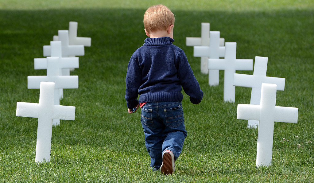 . Jason Mabon Jr., 2 runs past a row of flags during a memorial service for fallen service members Friday May 17, 2013 in front of the Memorial Chapel at the University of Redlands. Mabon\'s father, Jason Mabon, is an Air Force Reservist attending the university. The ceremony featured a special tribute to Keith Taylor, a University of Redlands alumnus and father of a University of Redlands student. He was killed serving in Iraq. (Rick Sforza/Staff photographer, Redlands Daily Facts)
