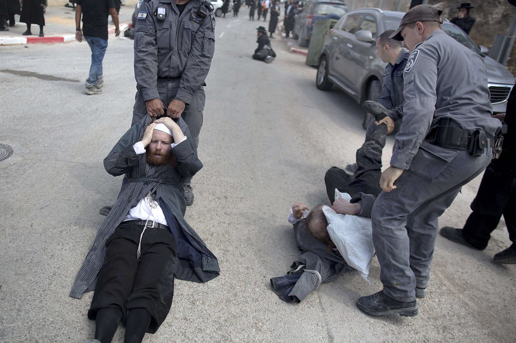 . Ultra-Orthodox Jewish men are dragged away by Israeli policemen in Ramat Beit Shemesh West of Jerusalem on August 12 2013, after dozens of Haredim protest against desecration of ancient graves were discovered at a new housing construction site. Some 14 Ultra-orthodox Jews were arrested.   MENAHEM KAHANA/AFP/Getty Images