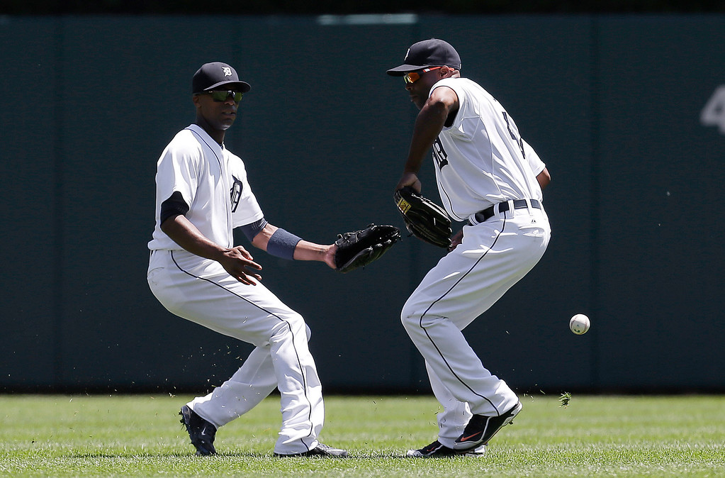 . Detroit Tigers right fielder Torii Hunter, right, drops a Toronto Blue Jays\' Jose Bautista fly ball as Austin Jackson, left, watches in the fourth inning of a baseball game in Detroit, Thursday, June 5, 2014. Bautista ended up on second base. (AP Photo/Paul Sancya)