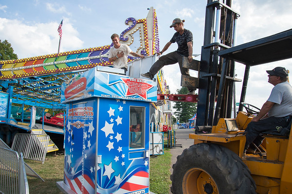09/11/19 Wesley Bunnell | StaffrrCarnival workers assemble attractions ahead of the Berlin Fair taking place this weekend. Jeremiah Delorme, L, Braxton Claire stand on top of a ticket booth as they complete the set up as forklift driver Phillip Sola looks on.