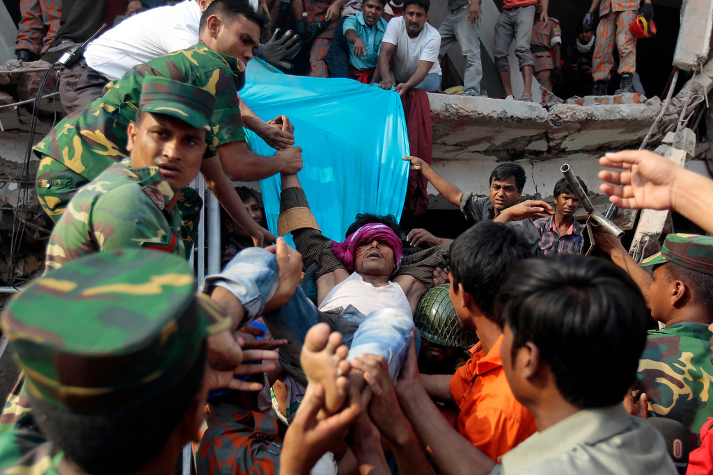 . Rescuers carry a survivor out from the debris of a building that collapsed in Savar, near Dhaka, Bangladesh, Wednesday, April 24, 2013. (AP Photo/A.M.Ahad)
