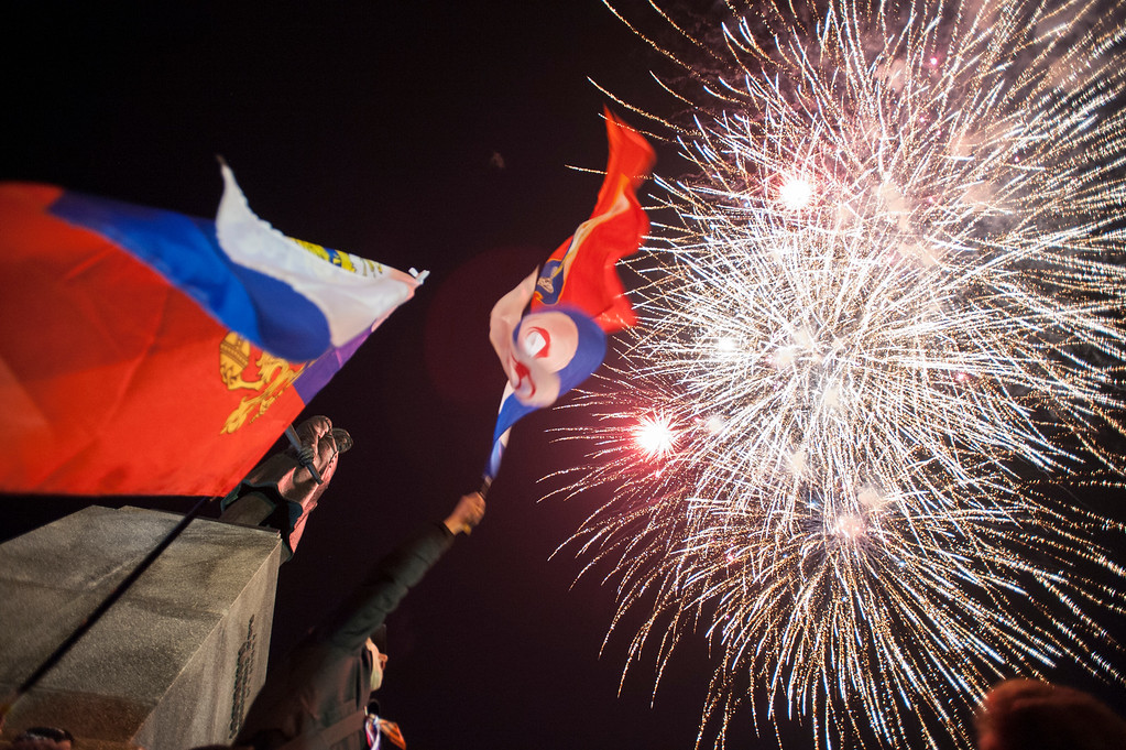 . People watch fireworks at the central Nakhimov square in Sevastopol, Crimea, on Friday, March 21, 2014.  Russian President Vladimir Putin completed the annexation of Crimea on Friday, signing a law making the Black Sea peninsula part of Russia. (AP Photo/Andrew Lubimov)
