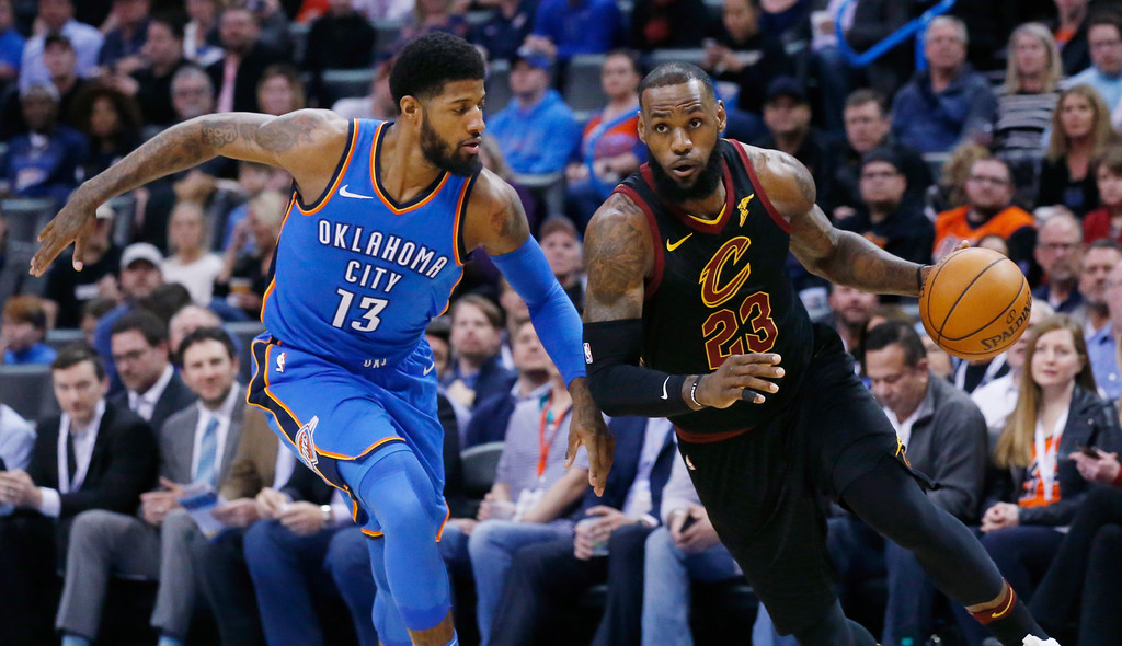 . Cleveland Cavaliers forward LeBron James (23) drives past Oklahoma City Thunder forward Paul George (13) during the first half of an NBA basketball game in Oklahoma City, Tuesday, Feb. 13, 2018. (AP Photo/Sue Ogrocki)