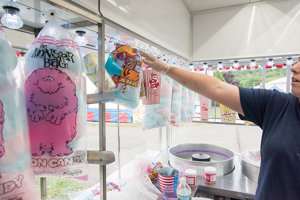 09/13/18 Wesley Bunnell | Staff Angela Belen hangs packages of cotton candy on Thursday afternoon in anticipation of opening night at the Berlin Fair.